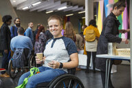 Portrait smiling, confident woman in wheelchair using smart phone at conference - CAIF20922