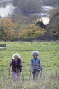 Active senior women friends hiking with poles up rural hillside - CAIF20934