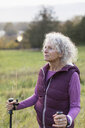 Thoughtful active senior woman hiking with poles in rural field - CAIF20937