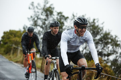 Smiling male cyclist cycling with friends - CAIF20955