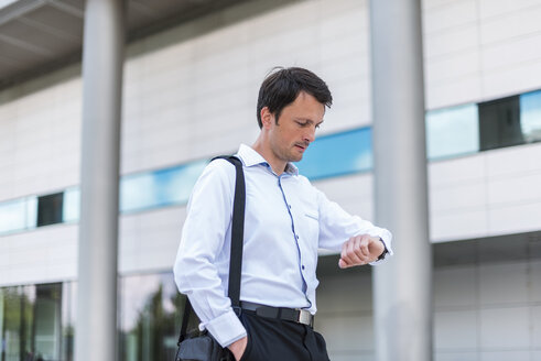 Businessman in the city checking the time - DIGF04670