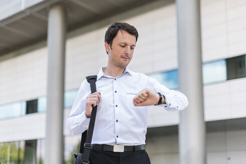 Businessman in the city checking the time - DIGF04673
