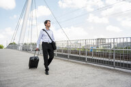 Businessman in the city with rolling suitcase crossing a bridge - DIGF04682