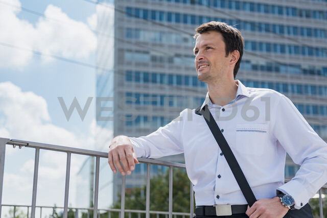 Smiling businessman in the city looking around - DIGF04688