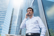 Businessman on cell phone in the city - DIGF04691