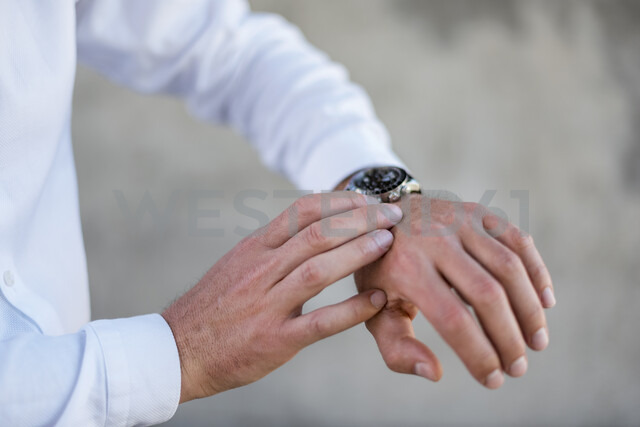 Close-up of businessman checking the time - DIGF04706