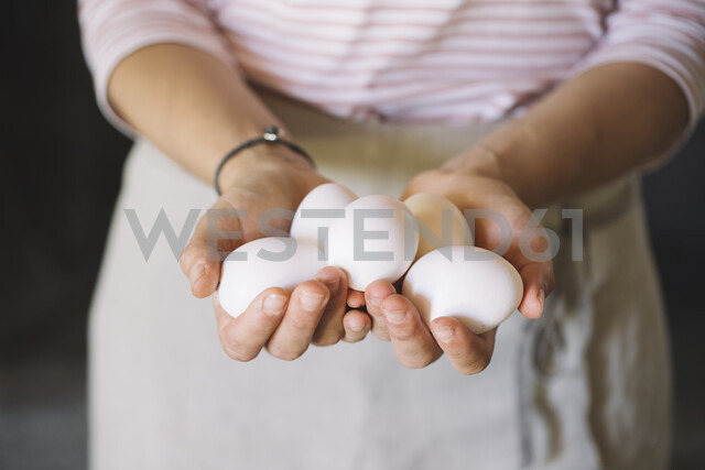 Woman holding raw white eggs - ALBF00486