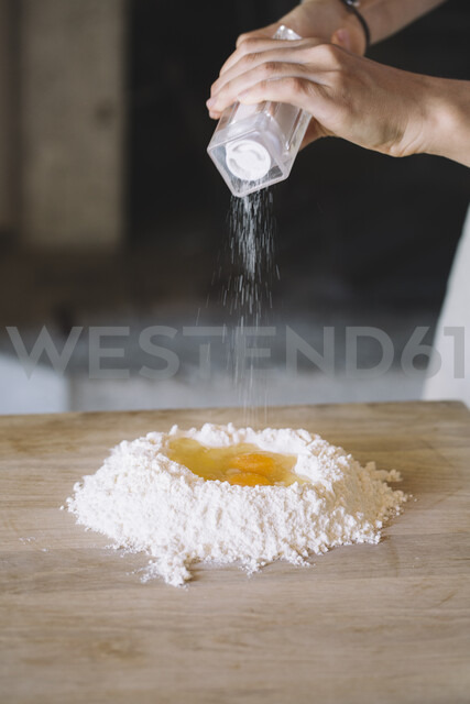 Woman salting eggs and flour on pastry board - ALBF00489
