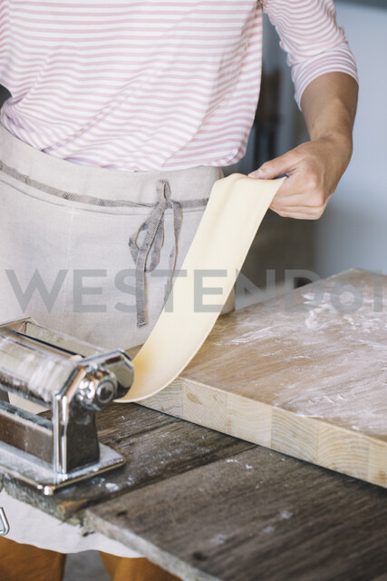 Woman preparing homemade pasta, using pasta maker - ALBF00498