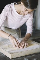 Woman preparing ravioli, pasta dough cutting out on pastry board - ALBF00501