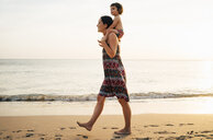 Thailand, Krabi, Koh Lanta, Mother with little daughter on her shoulders on the beach at sunset - GEMF02079
