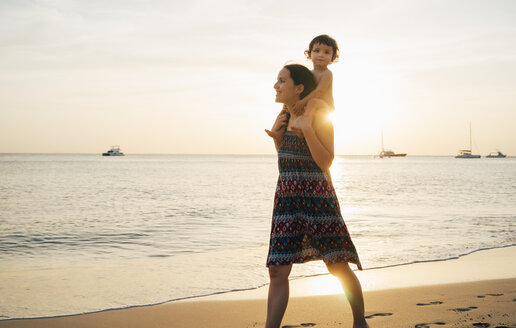 Thailand, Krabi, Koh Lanta, Mother with little daughter on her shoulders on the beach at sunset - GEMF02082