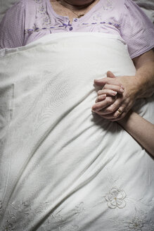 Cropped images of young woman holding sleeping senior woman's hand - CUF32393