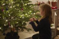 Young girl decorating christmas tree - CUF32438