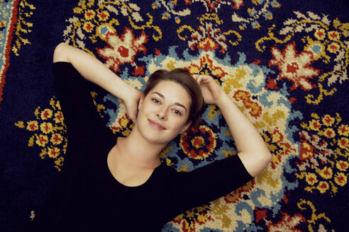 Portrait of young woman lying on patterned rug - CUF32471