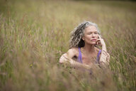 Mature woman sitting in long grass looking away - CUF32621