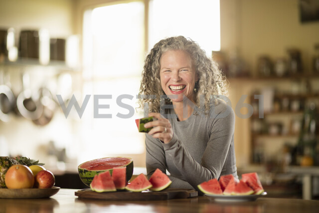 Portrait of mature woman eating watermelon in kitchen - CUF32633