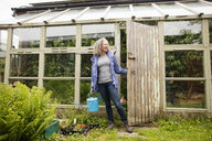Mature woman carrying watering can opening greenhouse - CUF32636