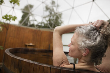 Mature woman with hands in hair in hot tub at eco retreat - CUF32639