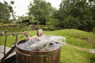 Mature woman jumping into fresh cold water tub at eco retreat - CUF32645