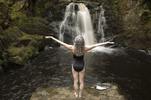 Rear view of mature woman practicing with open arms in front of waterfall - CUF32648