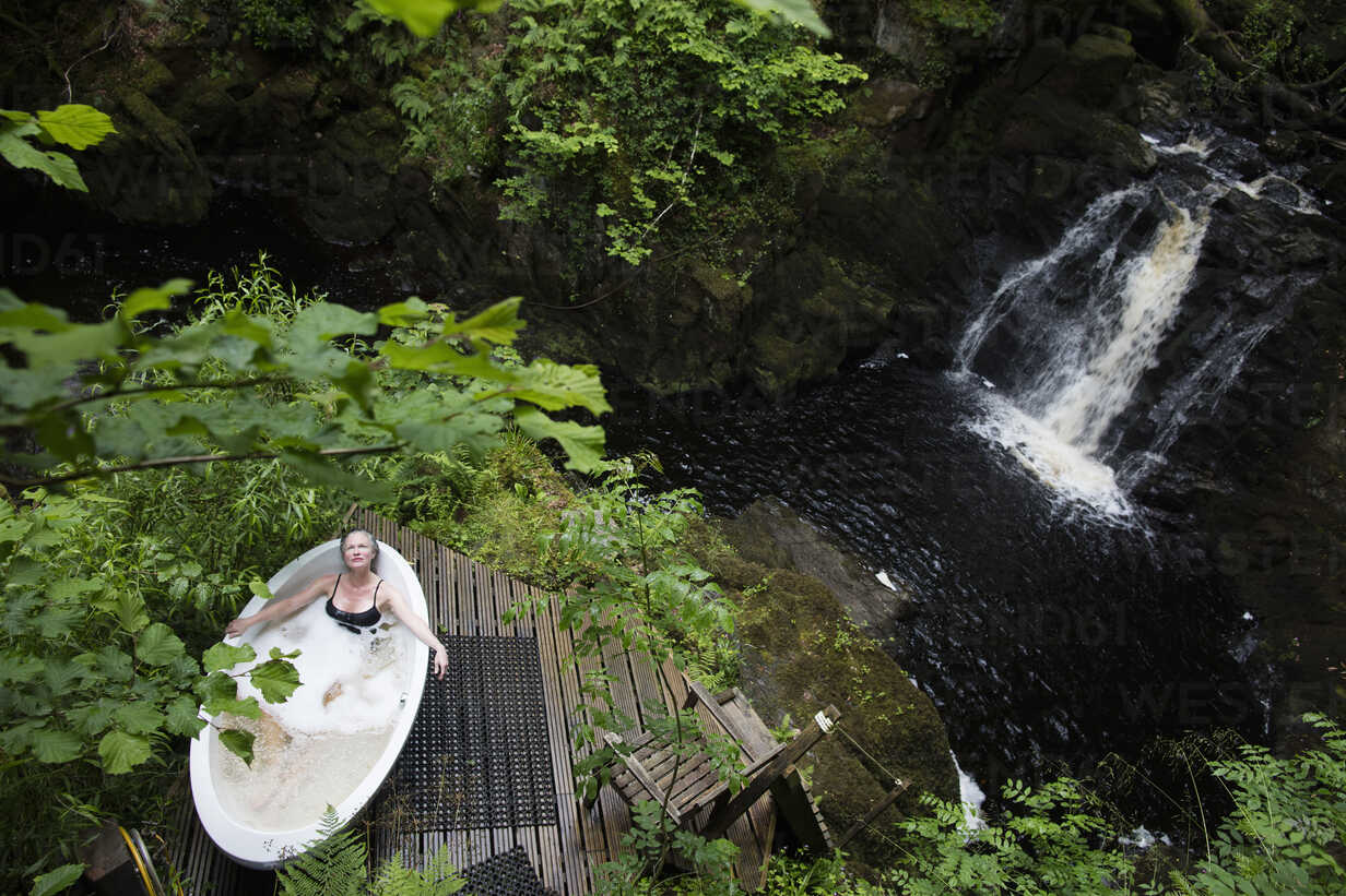 High angle view of mature woman in bubble bath in front of waterfall at eco retreat - CUF32651 - Leon Harris/Westend61