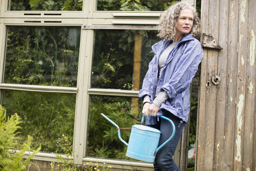 Portrait of mature woman with watering can leaning against greenhouse - CUF32657