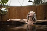 Mature woman relaxing in hot tub at eco retreat - CUF32660