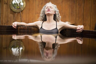 Mature woman meditating with eyes closed in hot tub at eco retreat - CUF32663
