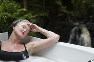Mature woman with eyes closed in bubble bath in front of waterfall at eco retreat - CUF32666