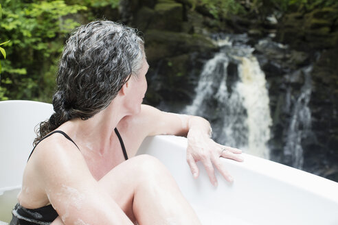 Mature woman in bubble bath gazing at waterfall at eco retreat - CUF32669
