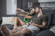 Young couple on sofa taking smartphone selfie - CUF32962