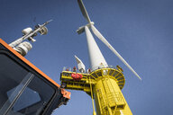 Engineers climbing wind turbine from boat at offshore windfarm, low angle view - CUF32971