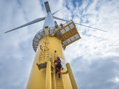 Engineers climbing wind turbine from boat at offshore windfarm, low angle view - CUF32974