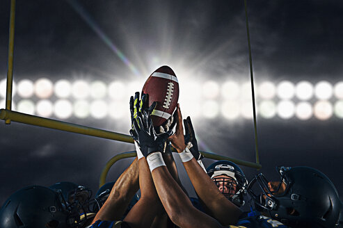 Victorious teenage and young male american football team holding up ball at night - ISF10471