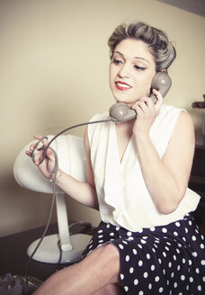 Portrait of young woman wearing vintage clothes and talking on vintage phone - CUF33010