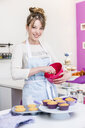 Woman preparing topping for cupcakes - CUF33019