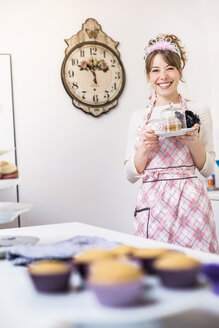 Woman holding up plate of homemade cupcakes - CUF33022