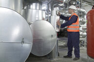 Technician monitoring pipes in power station - CUF33061