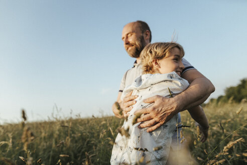 Father and son standing on a meadow hugging each other - KMKF00363