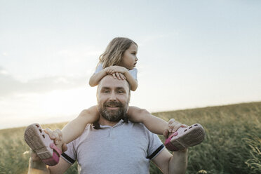 Portrait of smiling mature man in nature carrying little daughter on his shoulders - KMKF00375