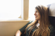 Young female tourist gazing out of train carriage window, Macau, Hong Kong, China - CUF33159