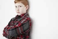 Boy crossing arms leaning against wall - ISF10523