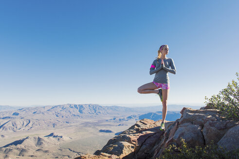 Young female trail runner doing yoga pose on Pacific Crest Trail, Pine Valley, California, USA - ISF10592