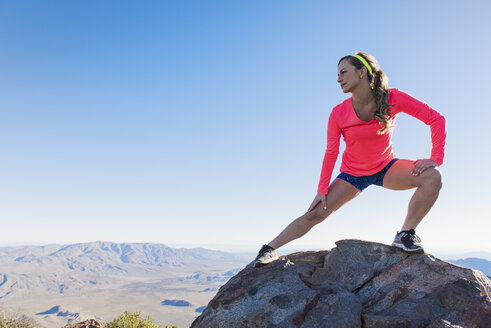 Young female trail runner stretching on rock on Pacific Crest Trail, Pine Valley, California, USA - ISF10595
