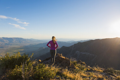 Young female trail runner looking at view on Pacific Crest Trail, Pine Valley, California, USA - ISF10601