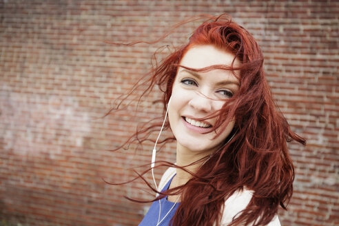 Young woman with long red hair, wearing earphones, close-up - ISF10651