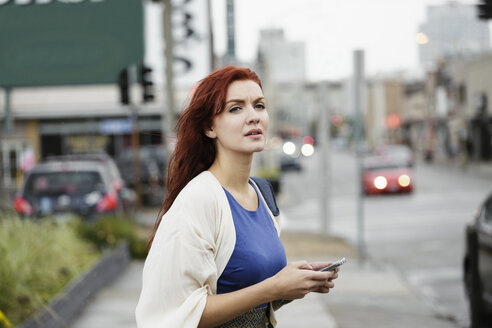 Young woman with long red hair, using smartphone in street - ISF10654
