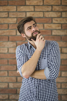 Portrait of bearded young man in front of brick wall thinking - AWF00058