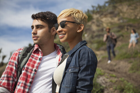Young couple, outdoors, looking at view, friends trailing behind - ISF10706